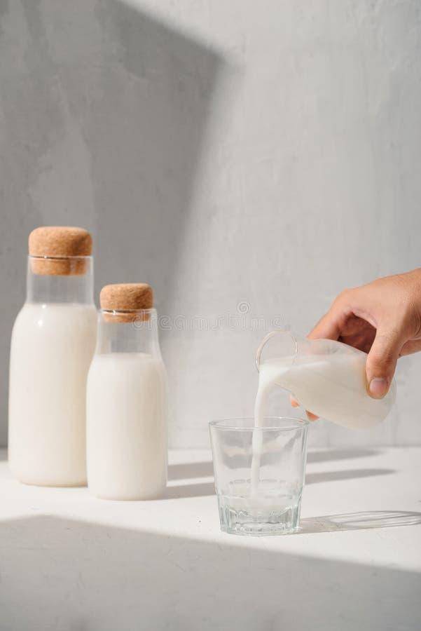 Milch von einem Krug, der in Glas gie?t lizenzfreie stockfotografie