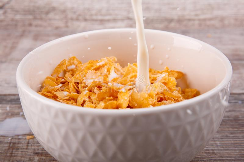 Milch wird in eine weiße Platte mit Corn Flakes gegossen lizenzfreies stockbild