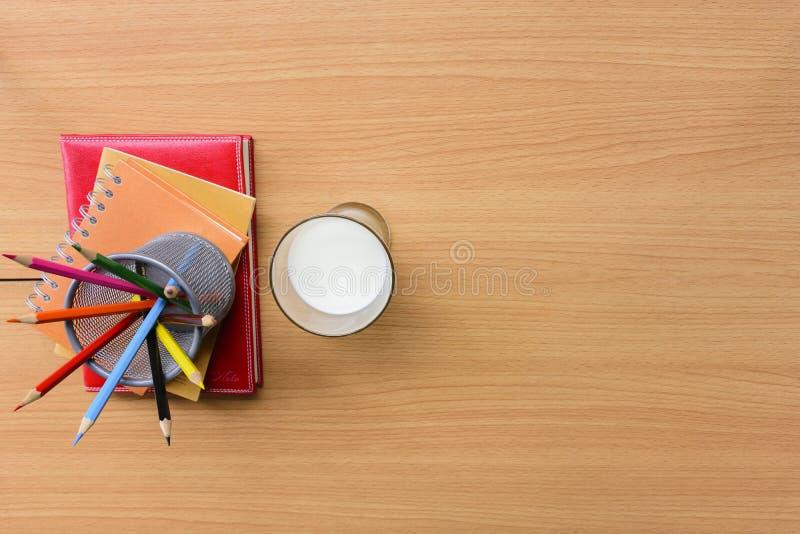 Milchglas mit Notizbuch und Farbe zeichnen auf Holztisch an Beschneidungspfad eingeschlossen stockfotografie