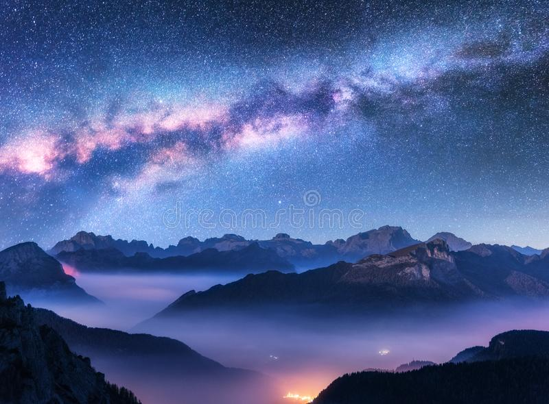 Milchstraße über Bergen im Nebel nachts im Herbst stockbilder