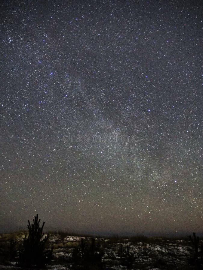 Milchstraßesterne auf nächtlichem Himmel und Schnee auf Seeküste lizenzfreie stockbilder
