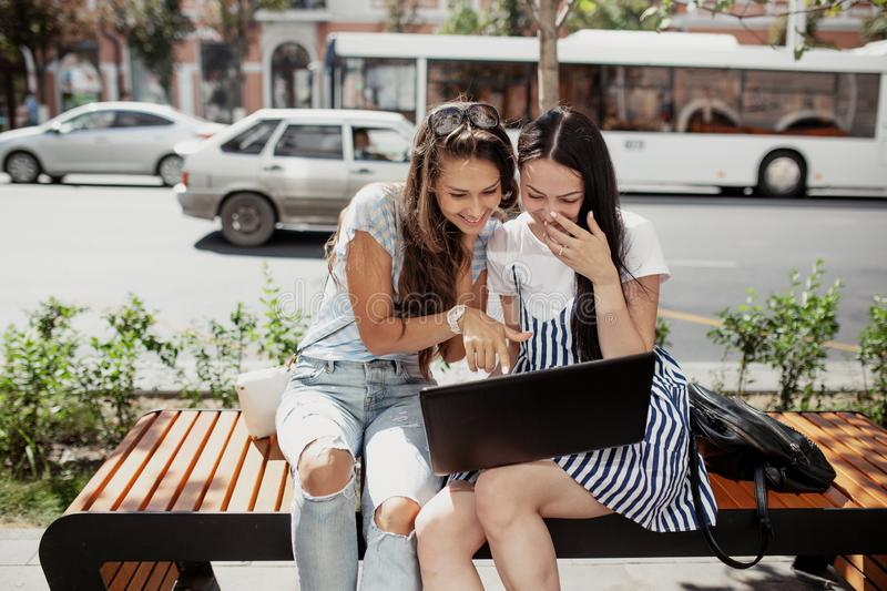 On a mild day, two beautiful girls with dark hair,wearing casual outfit, sit on the bench and laugh. royalty free stock photography