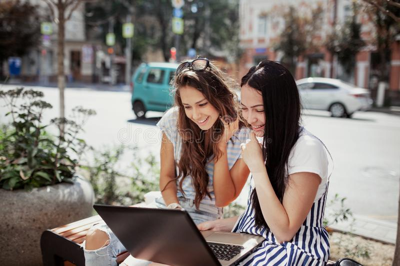 On a mild day, two cute slim girls with long dark hair,wearing casual style,sit on the bench and look attentively at the royalty free stock image