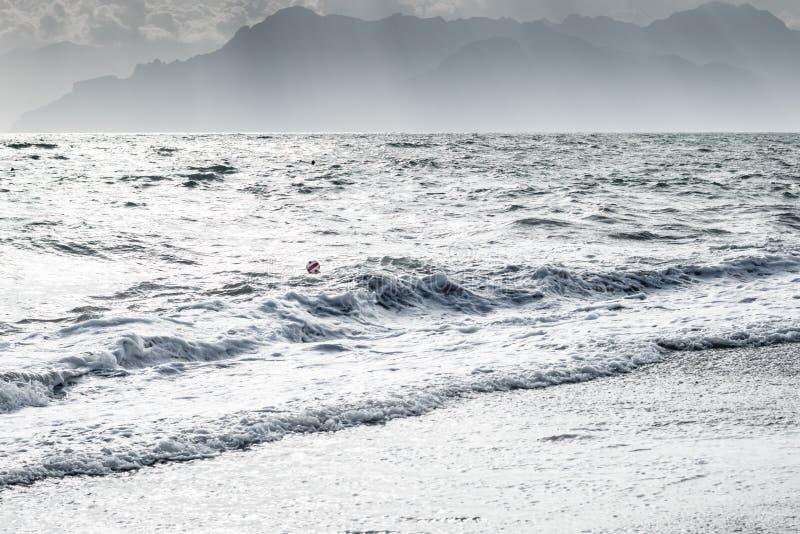 Milde Meereswellen und weißes Ufer mit einem Ball auf Wasser und Bergsilhouette lizenzfreies stockbild