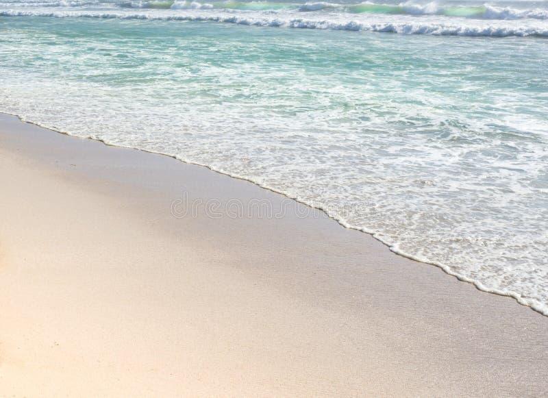 Mildern Sie Wellenkräuselungen von blauem Ozean auf sandigem Strand stockbild