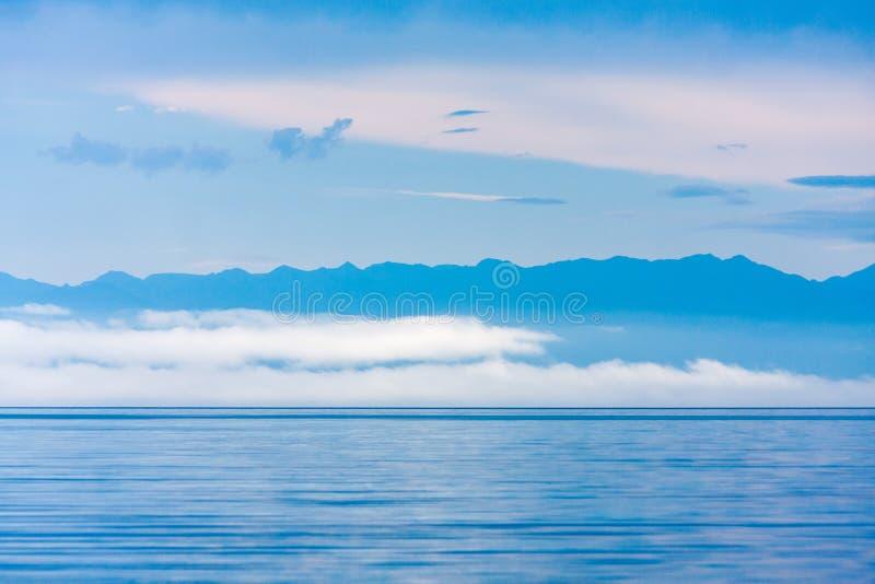 Mildra mist över sjön, med låga moln och bergkonturer royaltyfria foton