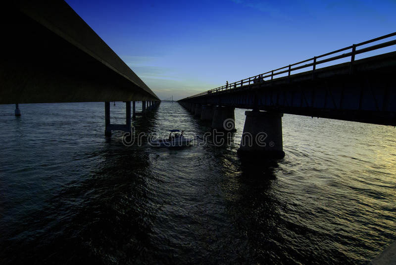 7 mile bridge. The old and new 7 mile bridge looking down between them with a gold sky to the right and blue to the left stock images