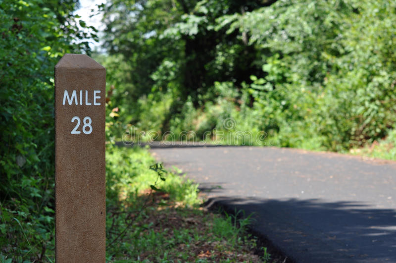 Mile marker along a biking path. A post marking mile 28 along a biking and jogging path stock photos
