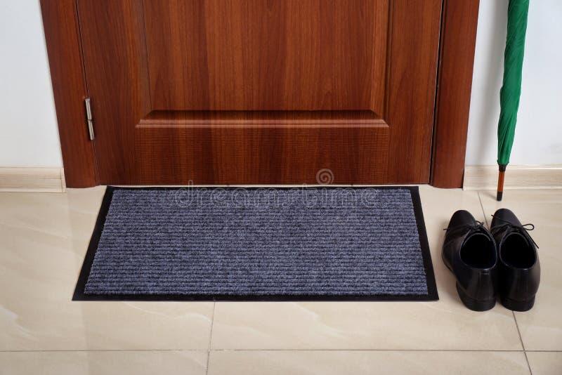 Mile widziany mata, samiec buty i parasol przy drzwi, obrazy stock