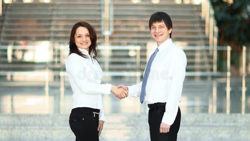 Mile widziany uścisk dłoni młodzi partnery biznesowi na tle biuro zdjęcia stock