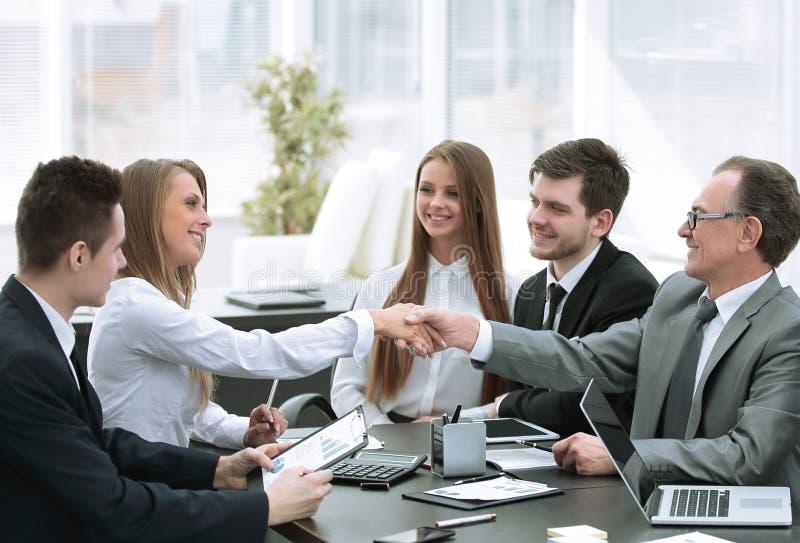 Mile widziany uścisk dłoni partnery biznesowi przy stołem negocjacyjnym obraz stock