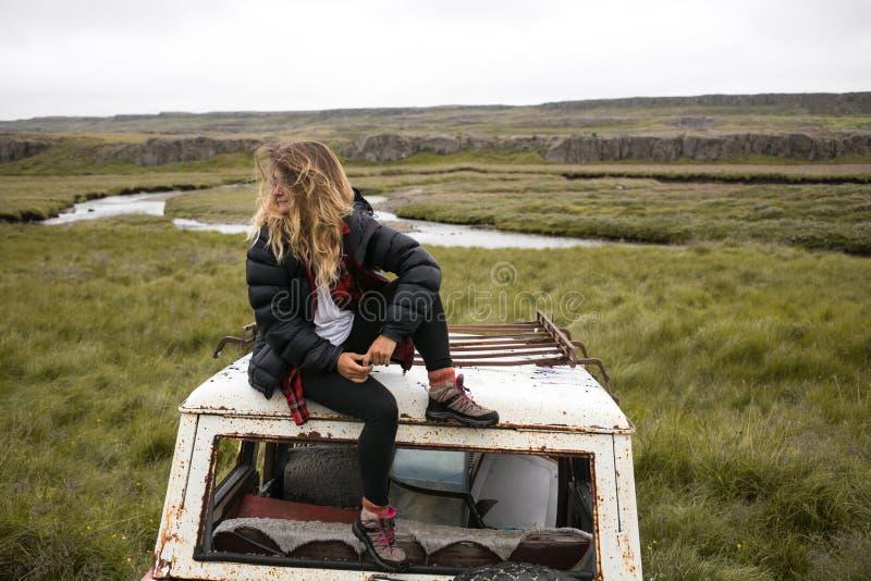 Milenar na moda dos jovens na jarda de sucata velha do carro imagem de stock