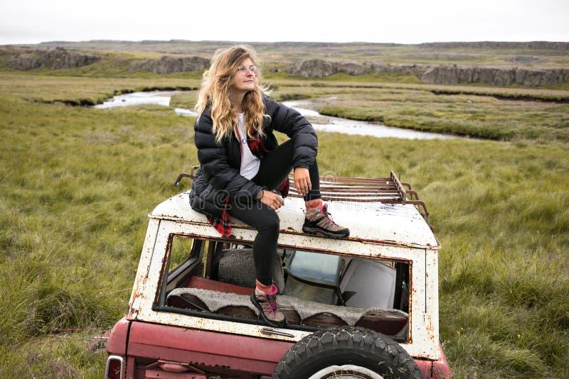 Milenar na moda dos jovens na jarda de sucata velha do carro fotos de stock royalty free