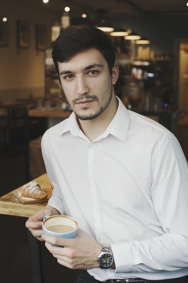 Milenario confiado joven comiendo un café fotos de archivo