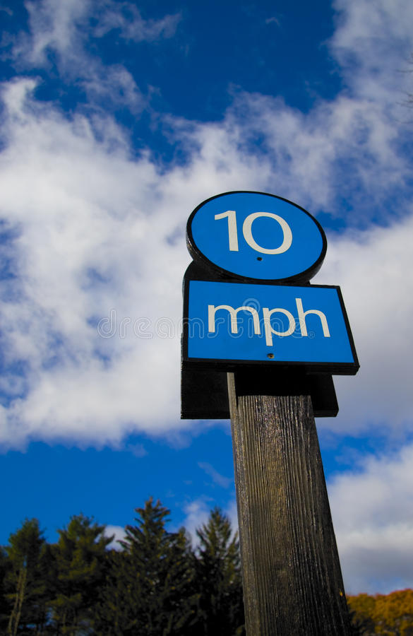 10 miles per hour sign. Blue 10mph (miles per hour) sign on wooden post with cloudscape background, deCordova Sculpture Park and Museum, Massachusetts, U.S.A royalty free stock photo