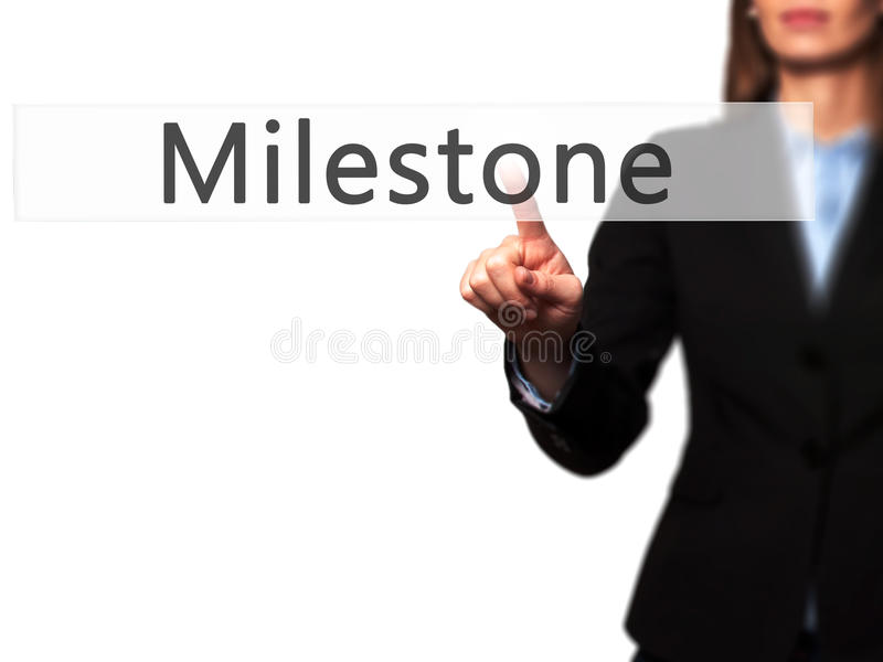 Milestone - Businesswoman hand pressing button on touch screen stock photography