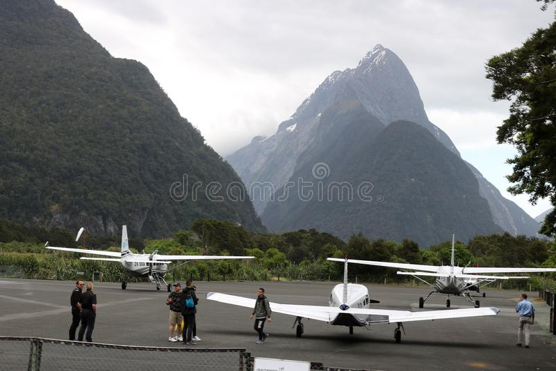 Milford Sound airport and Mitre Peak New Zealand. View of four light aircraft on the tarmac at the small Milford Sound airport in Fiordland, South Island, New royalty free stock photo