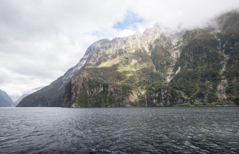 Milford Sound est une merveille naturelle de renommée mondiale avec les crêtes de domination, les cascades de cascade et la faune images libres de droits