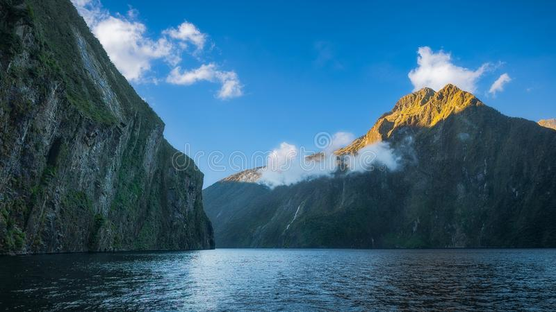 Sheer Cliffs at Milford Sound in New Zealand. Milford Sound is incredibly grand and the fiord`s sheer cliffs excite both admiration and apprehension - Fiordland stock photography
