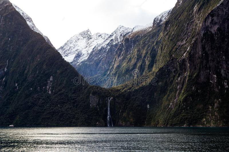 Milford Sound Snow Covered Mountainin Peaks with Waterfall royalty free stock photo