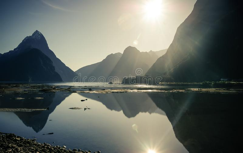 Milford sound stunning mountain views from the lake and the reflection of the sky and a sunny ray of light stock photo