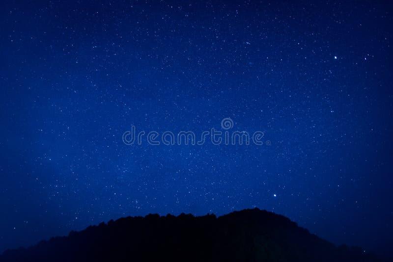Milhões de estrelas brilham no céu da escuridão no fundo bonito da natureza imagens de stock