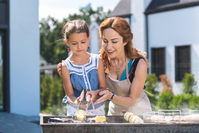 Milho agradável alegre do churrasco da mãe e da filha foto de stock