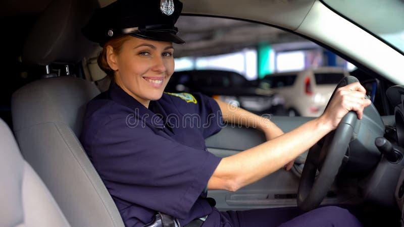 Milicyjna kobieta w jednolitym obsiadaniu w radiowozie i ono uśmiecha się kamera, na obowiązku fotografia stock