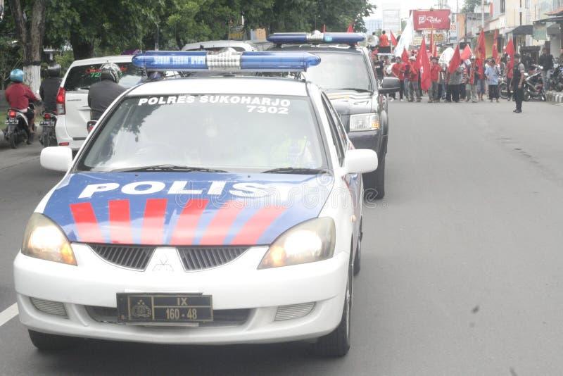 Milicyjna Utrzymuje Tradycyjna Targowa handlowiec akci demonstracja Sukarno w Sukoharjo obrazy stock