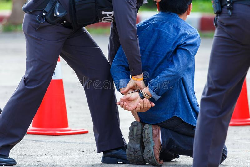 Milicyjni stal kajdanki, Milicyjny aresztujący, Fachowy funkcjonariusz policji, muszą być bardzo silni, oficera Aresztować zdjęcia stock