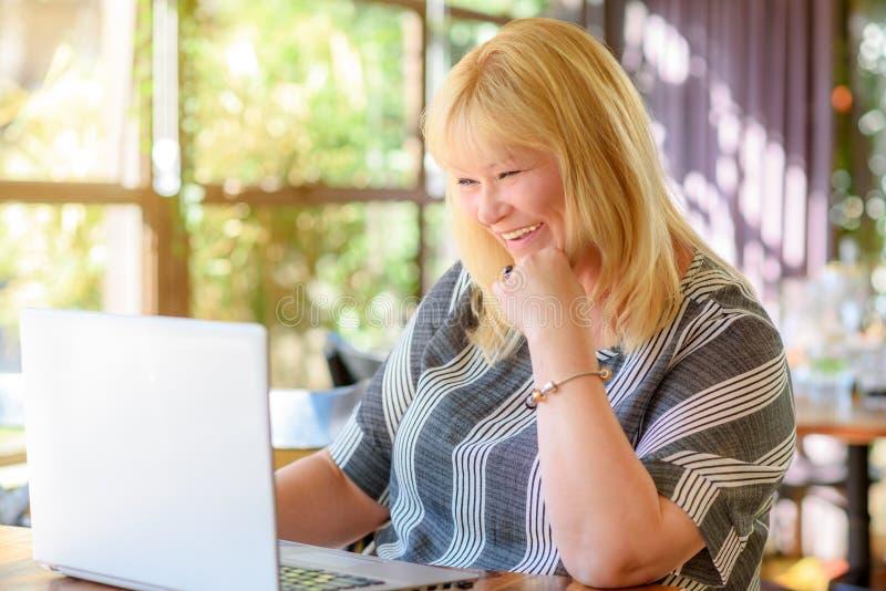 Milieu élégant de portrait âgé plus la femme d'affaires de taille travaillant sur l'ordinateur portable en bureau ou café créatif photo stock