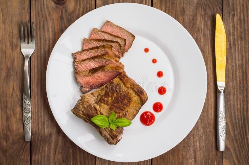 Milieu rare de bifteck de boeuf grillé avec de la sauce barbecue Table en bois Vue supérieure Plan rapproché photographie stock libre de droits