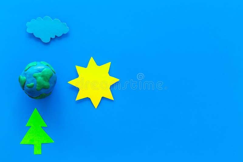Milieubeschermingconcept Plastilinesymbool van aarde en zon, wolk, boom coutout op blauwe bovenkant als achtergrond royalty-vrije stock foto's