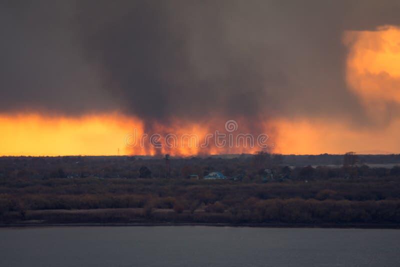 Milieuprobleem van brand op droog die gras met rook op de horizon door een sterke wind tijdens de zonsondergang wordt opgeblazen royalty-vrije stock afbeeldingen