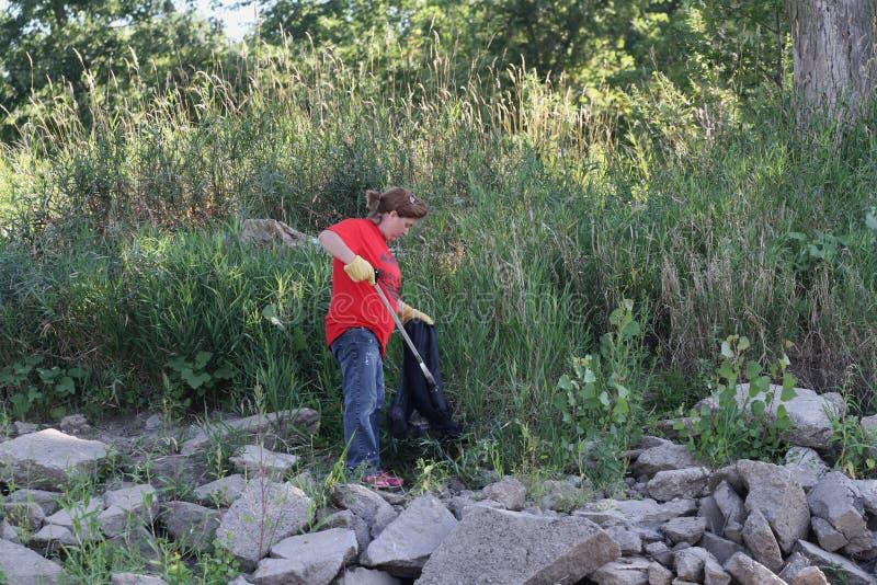 Milieuschoonmaak langs een rivier stock fotografie