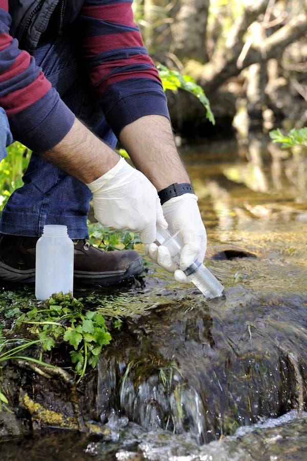 Milieuvervuilingstudie van een watercursus stock foto's