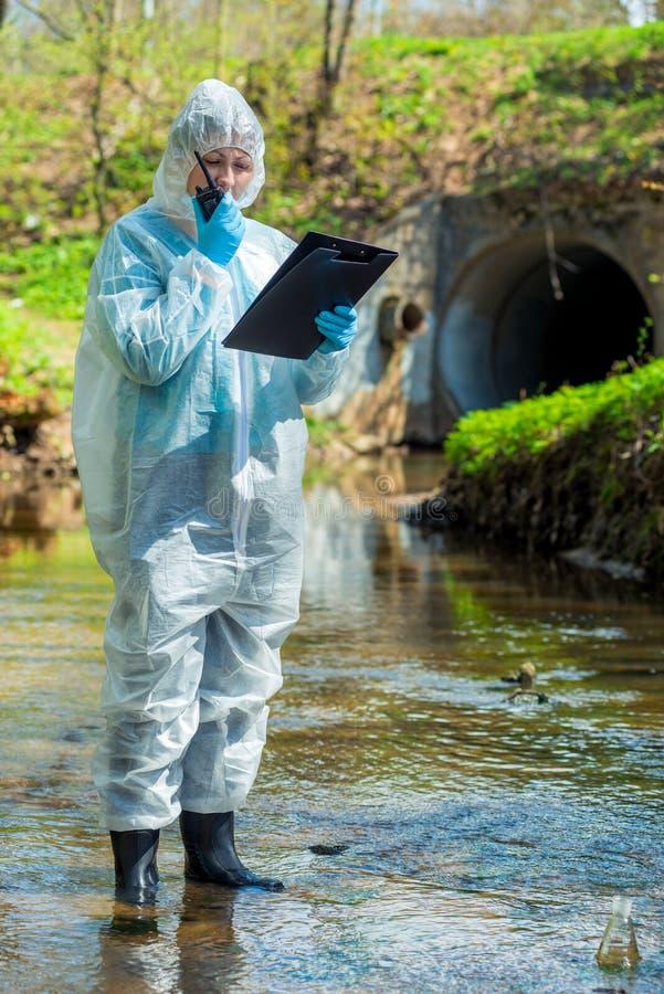milieuwetenschapper met een walkie-talkie en een notitieboekje op de achtergrond van een riool stock foto