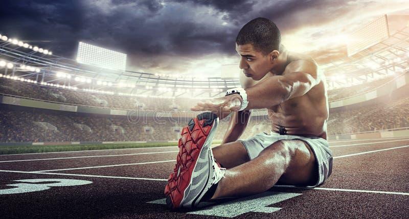 Milieux de sport Coureur s'étendant sur la la ligne de début image stock