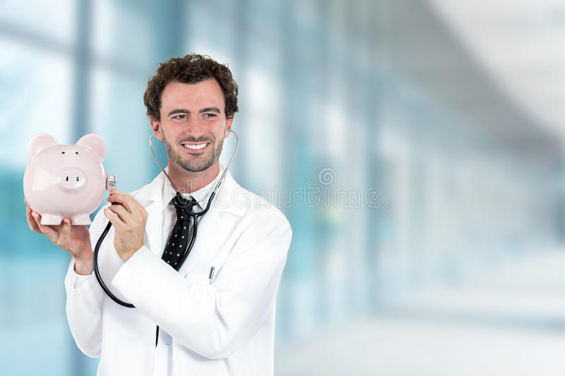 Miling doctor holding listening to piggy bank with stethoscope. Portrait happy smiling doctor holding listening to piggy bank with stethoscope standing in stock image
