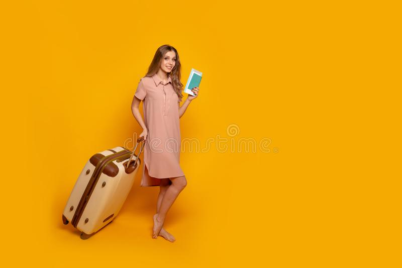 Miling woman traveler holding passport with ticket and credit card. yellow wall stock photography