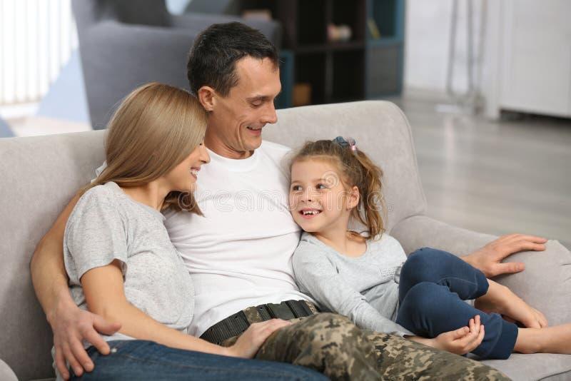 Militär fader med hans familj på soffan arkivbilder