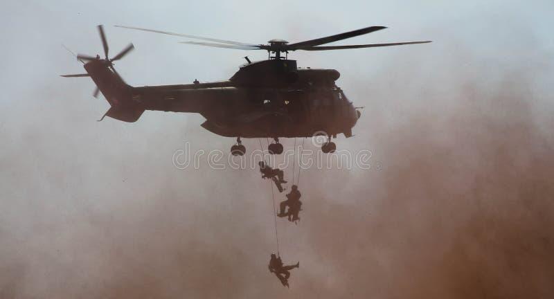Militär helikopter som tappar soldaten vid repet arkivbild