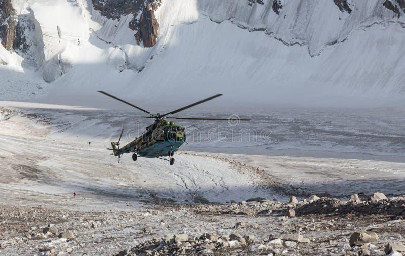 Militär helikopterlandning på is av berget som är mer galcier i nöd- läge royaltyfria foton
