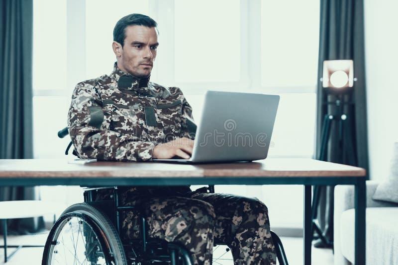 Militär man i rullstolarbeten på bärbara datorn arkivfoto
