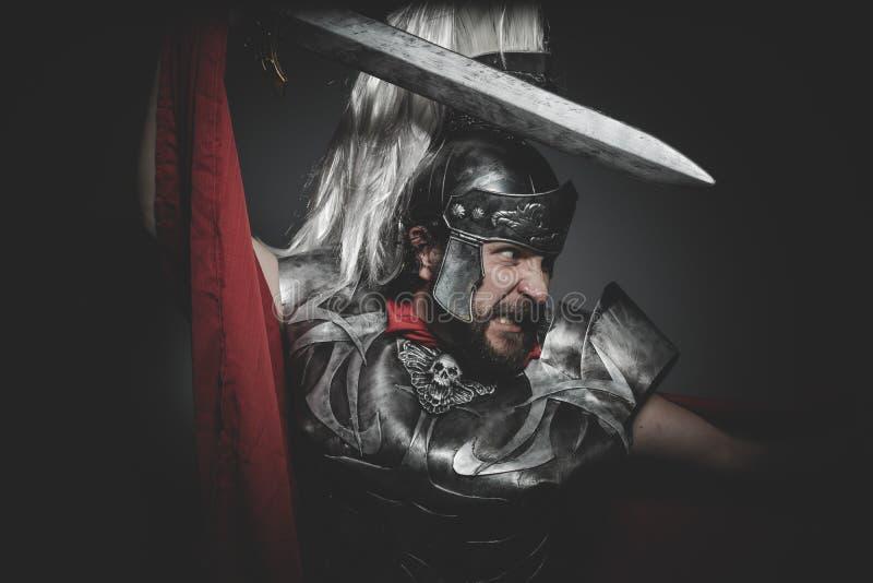 Militär, Praetorian romersk legionär och röd kappa, harnesk och strömbrytare arkivfoto