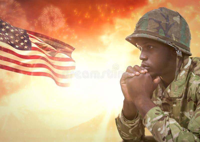 Militär som tänker mot solnedgång och amerikanska flaggan arkivbilder