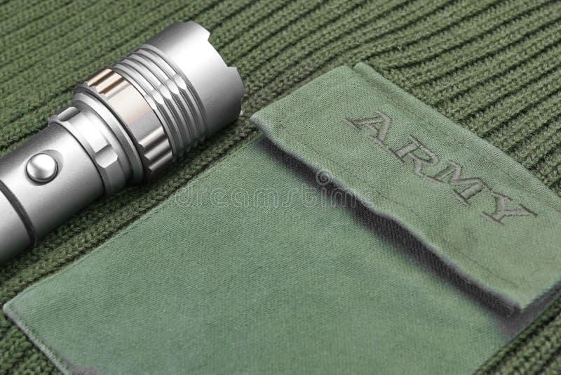 Militär tröja för kakifärg med armétecknet och silverfacklan arkivfoton