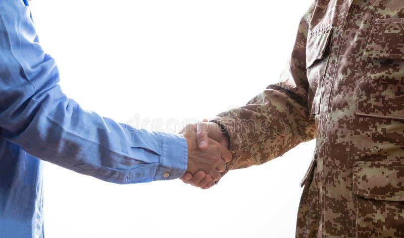 Militär- und rüttelnde Zivilhände, die auf weißem Hintergrund stehen lizenzfreie stockfotos