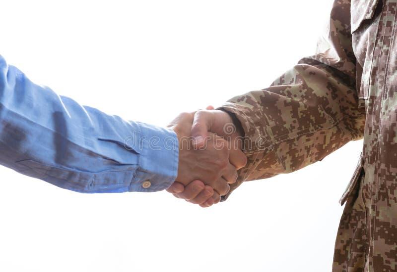 Militär- und rüttelnde Zivilhände, die auf weißem Hintergrund stehen lizenzfreies stockbild