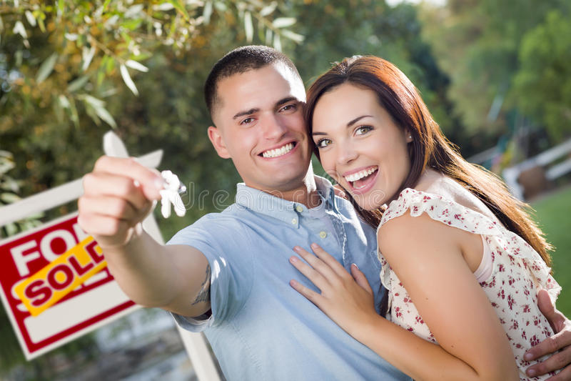 Militära par med hustangenter och det sålda Real Estate tecknet fotografering för bildbyråer
